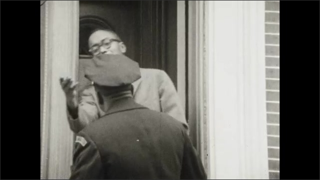 1950s: UNITED STATES: man stands at door. Police man visits house.