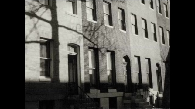 1950s: UNITED STATES: man repairs window. Man cleans window. Buildings in street. Renewal of community buildings.