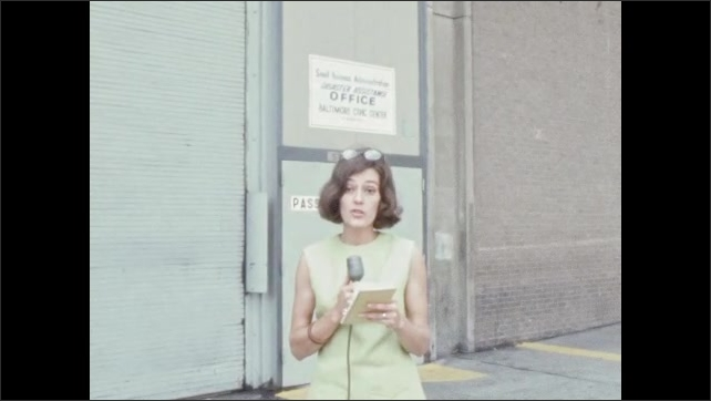 1970s: UNITED STATES: Baltimore Civic Centre Office. Lady speaks to camera outside office. Flood damage and clean up. Disaster centre.
