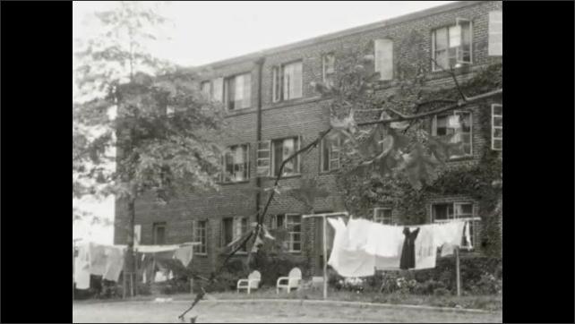 1940s: UNITED STATES: washing outside city building