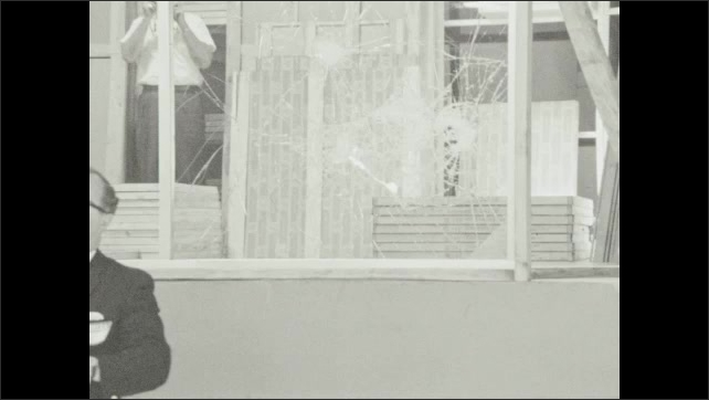 1960s: UNITED STATES: man with crowbar. Man hits glass with crowbar. Window cracks.