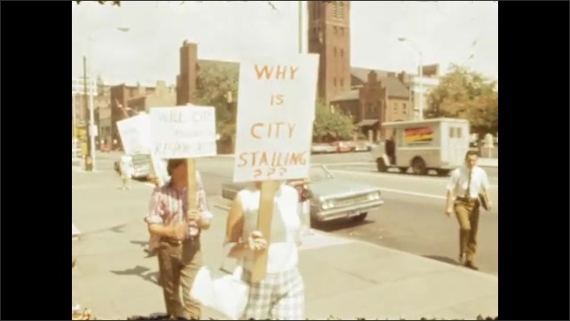 1970s: UNITED STATES: protesters carry banners in street. Why is the City Stalling? Banner. Men interviewed in street.