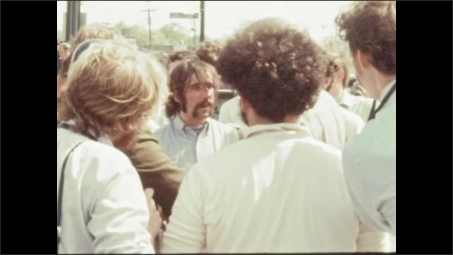 1970s: UNITED STATES: protesters and riot team line street. Man talks to military in street. Man takes photo.