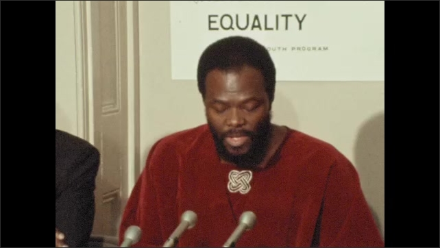 1970s: UNITED STATES: man speaks at press conference. Equality sign on wall.