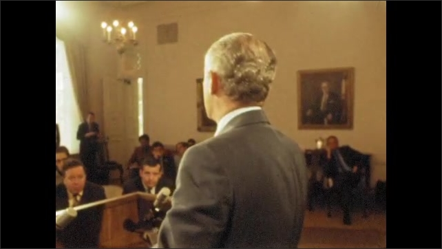 1970s: UNITED STATES: man addresses press at conference from podium. Man films conference with camera