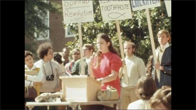 1970s: UNITED STATES: lady speaks at rally. People at peaceful protest. People with banners.
