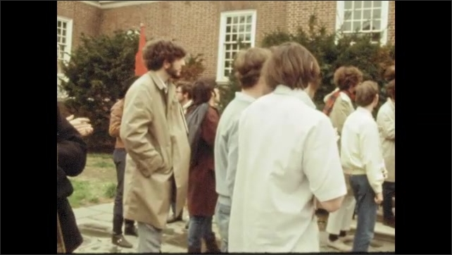 1970s: UNITED STATES: university students attend protest. People walk across grass with banners