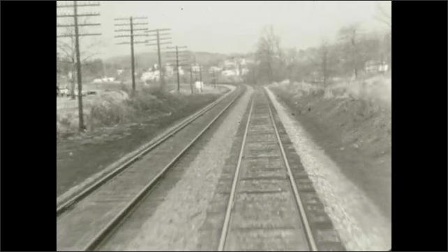 1970s: UNITED STATES: view along railway tracks from back of train. Embankment by railway line. Posts by railway tracks.