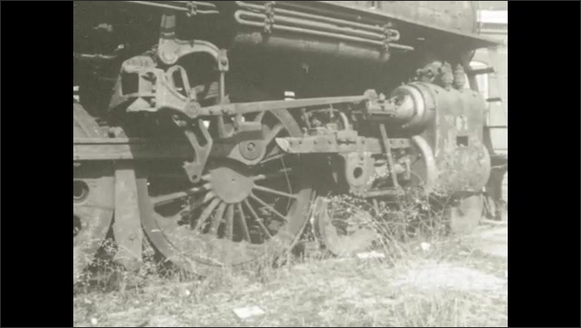 1970s: UNITED STATES: abandoned train and grass around wheels. Workings of train wheels.