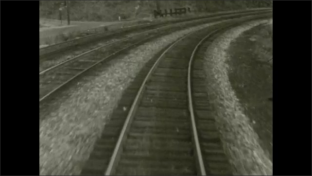 1970s: UNITED STATES: train tracks through woodland. View from front of train. Train travels over bridge