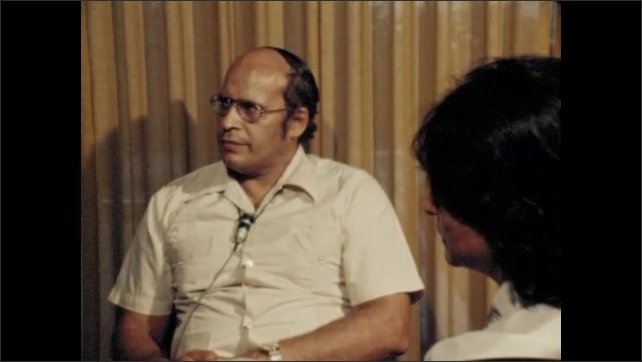 1970s: UNITED STATES: man sits by microphone and curtain. Man in glasses.