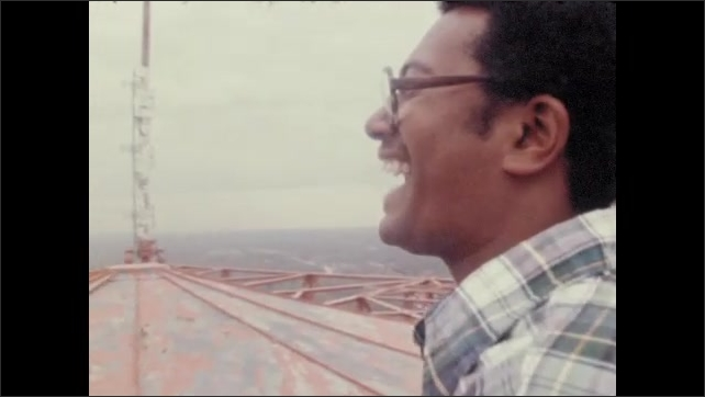 1970s: UNITED STATES: man smiles at top of tower. Man stands in cold breeze. Man smiles at panoramic view.