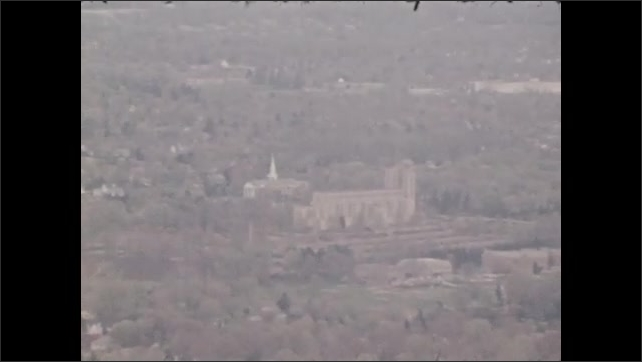 1970s: UNITED STATES: church building in distance. View of landscape from tower. Buildings and landmarks seen from tower