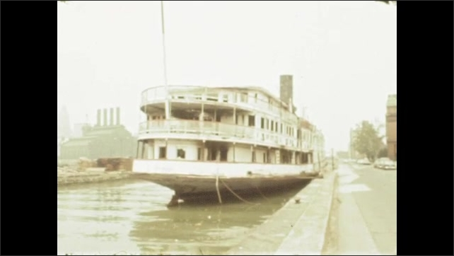 1970s: UNITED STATES: paddle steamer boat on water. Boat moored by path