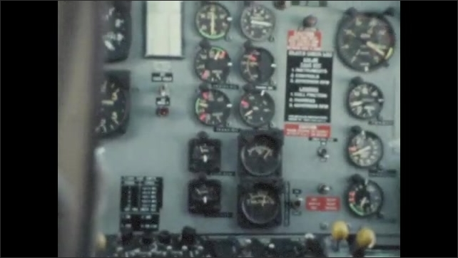 1970s: UNITED STATES: pilot flies helicopter. Rear view of helicopter pilot in helmet. Panels on helicopter panel. Writing on back of pilot's chair.