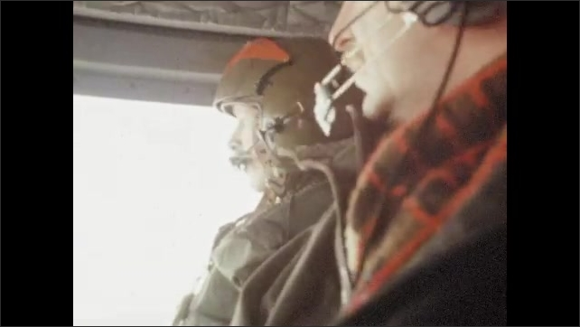 1970s: UNITED STATES: view of ground and snow from helicopter. Interior of helicopter. Men in helicopter in helmets. Helicopter pilot