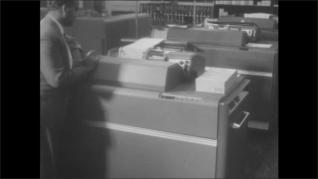 1960s: Man turns on computer, watches print out.