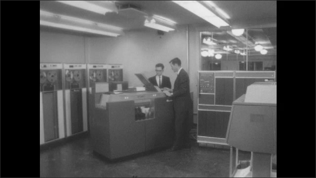 1960s: Close up of chart. Man writing on chalkboard. Men operating computer in lab.