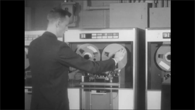 1960s: Man loads tape reels into computer.