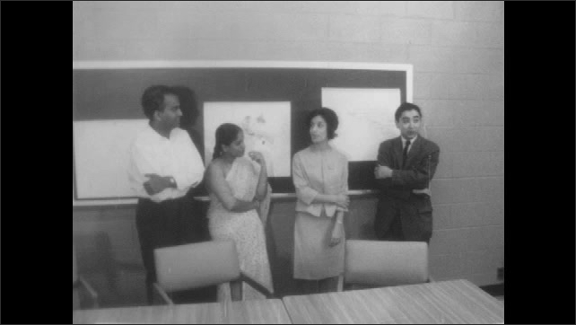 1960s: Man in front of chalkboard. Close up of man talking. People in front of chalkboard. Man and woman. Woman talking.