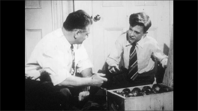 1950s: UNITED STATES: boy tries to open box with hands. Man shows tool to boy. Man smokes pipe. Man opens box. Machine and engine