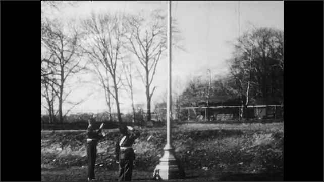 1950s: UNITED STATES: pulley system on crane. Arm of crane moves. Man raises flag on pole. Flag blows in wind