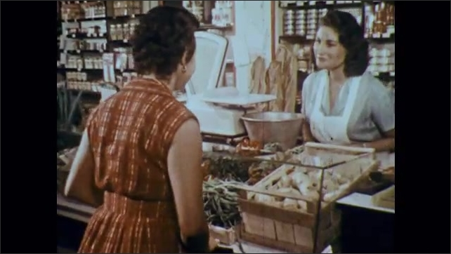 1960s: Woman adjusts display outside of shop. Woman enters shops, greets clerk. Woman speak French. Woman touches beans, talks to clerk.