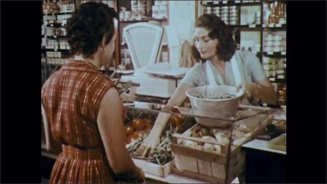 1960s: Woman speaks to woman behind grocery counter. Woman loads green beans into bowl.