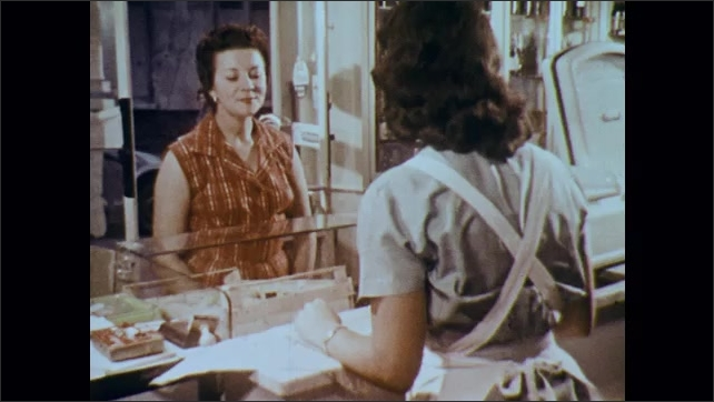 1960s: Woman speaks to woman behind counter. Clerk grabs baguette places it into woman's bag. Women talk. Woman tallies grocery bill.