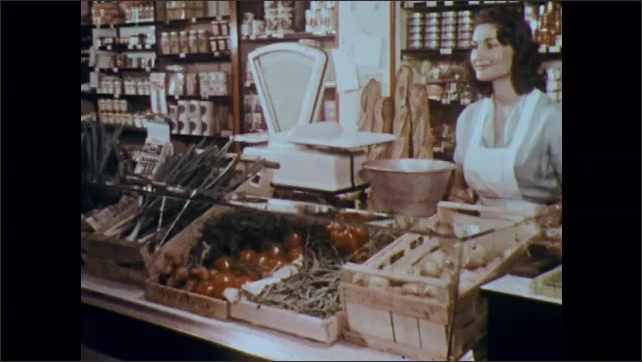 1960s: Woman pays grocer, leaves store.