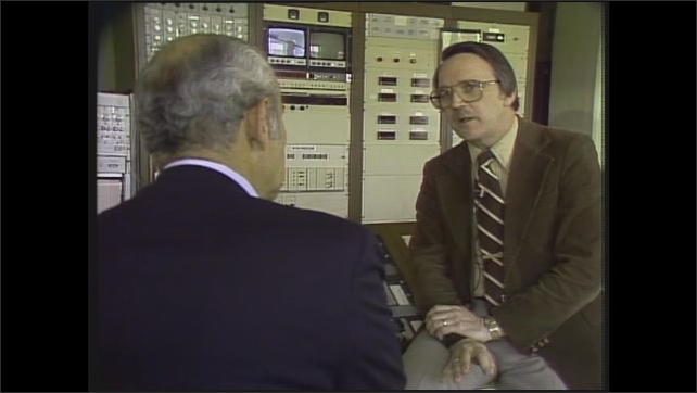 1980s: Control room.  Men speak.  Blades turn on wind turbine.