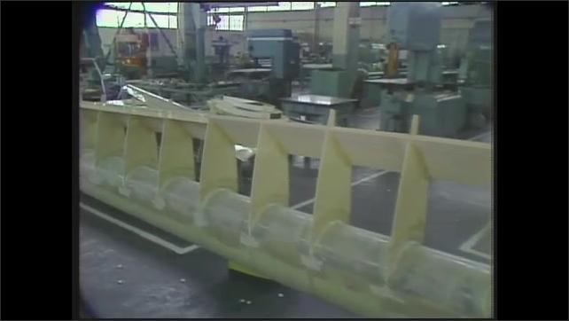 1980s: Warehouse.  Wind turbine blade.  Men speak.