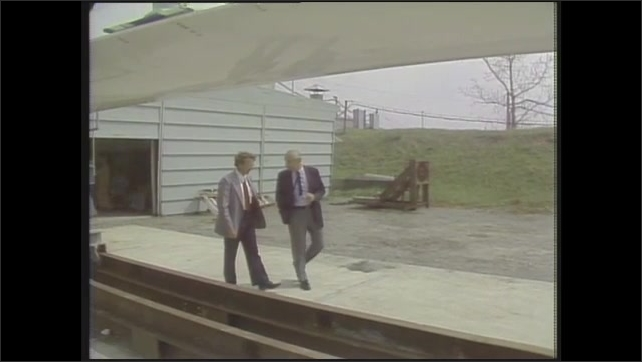 """1980s: Men walk and talk.  Wind turbine blade.  Caption reads """"Meade Gougeon.  Chairman Gougeon Brothers, Inc."""""""
