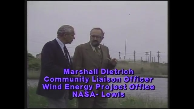 "1980s: Men talk.  Marsh.  Wind turbine blades spin.  Caption reads ""Marshall Dietrich, Community Liaison Officer, Wind Energy Project Office, NASA- Lewis."""