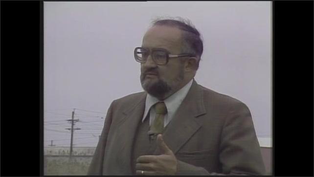 1980s: Wind turbine.  Men speak.