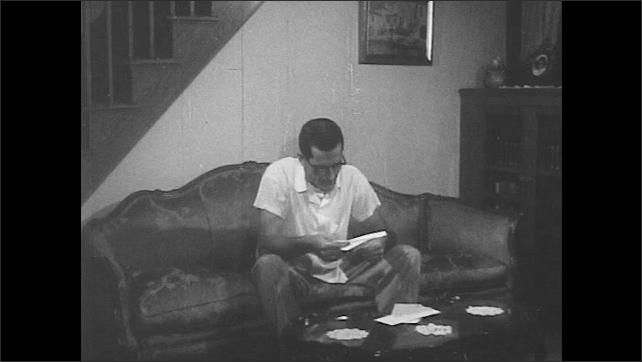 1950s: Man sits down on sofa and opens letter. Man reads letter and smiles.