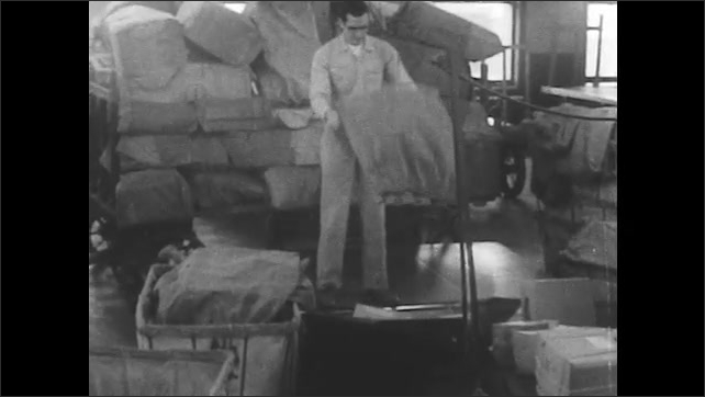1950s: Man pulls bag off trailer, opens it and dumps packages onto belt. Man sits down and shakes his head.