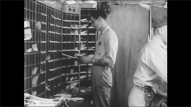 1950s: Employees sort letters into pigeonholes. U.S. Mail truck turns off street.