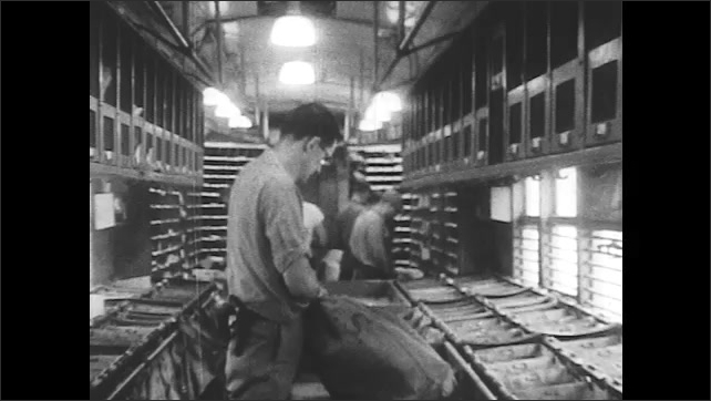 1950s: Worker loads mail into mail sack while other workers place letters in pigeonholes. Worker closes mail sack and carries it to end of train car.