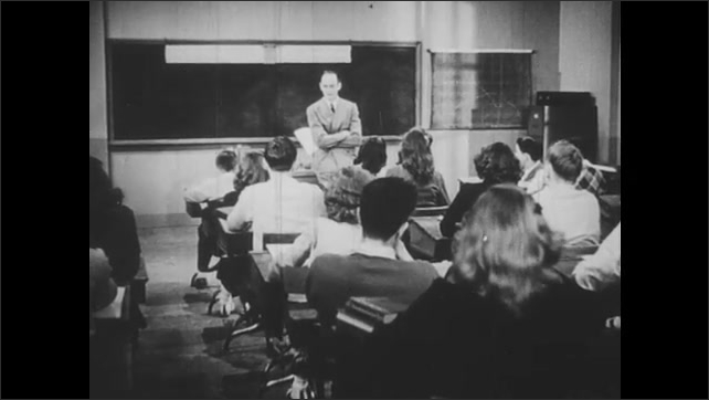 1940s: Teacher looks concerned as he talks to class.