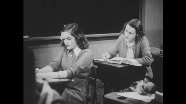 1940s: Students complain to each other. Teacher tells class to be quiet. Teacher writes on blackboard.