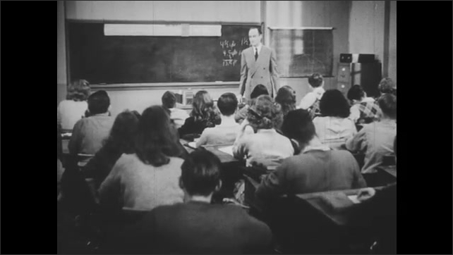1940s: Boy scratches his head and talks to girl beside him. Woman walks into classroom and hands note to teacher.