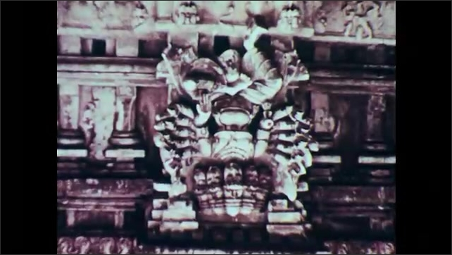 1960s: Woman in sari folds hands and bows hand in front of carved stone shrine. Ganesh and other Hindi statues carved in stone.