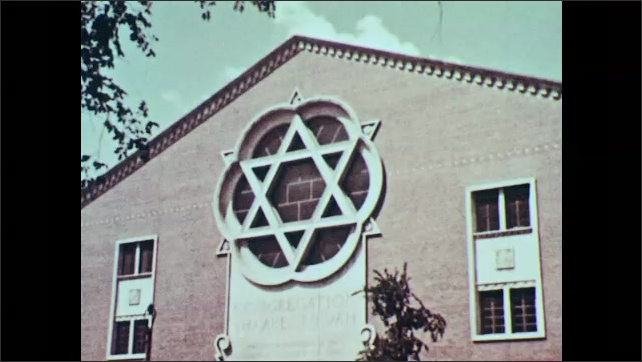 1960s: Exterior of Jewish synagogue with Star of David shaped window. Rabbi and men incant and pray.