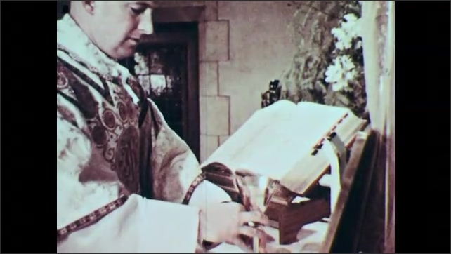 1960's Catholic Priest turns Bible on stand towards congregation. Altar boys fold hands in prayer. Priest prepares chalice.