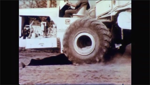 1960s: Tractor's wheel moves. Man drives tractor, the image freezes and a square appears in front of the wheel and disappears. Man drives tractor.