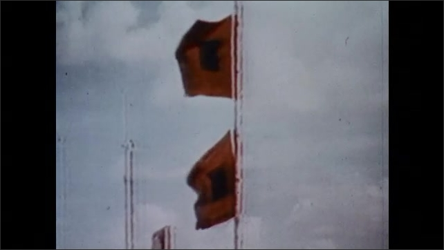 1970s: UNITED STATES: red flags fly to warn of hurricane. Hurricane warnings by coast. People leave town by car. Tourist on beach. Man speaks to tourist.