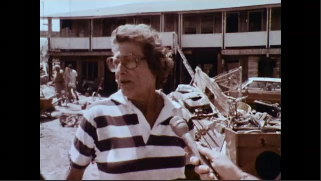 1970s: UNITED STATES: lady speaks to camera outside damaged building. Hand with microphone.