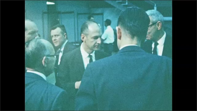 1960s: UNITED STATES: critical review of manned space flight. Spring 1967 review. Men talk together in suits