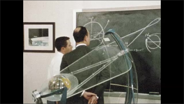 1960s: Scientist in lab. Man walks through computer server room. Science facility. Two men look at equation on chalk board. Men in meeting with models of lunar lander. Stage of rocket in warehouse.